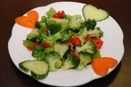 broccoli with green and red bell pepper slices on the white served plate