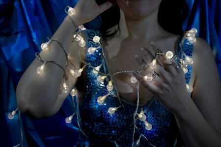 Smiling woman holds christmas decoration lights turned on shining in her arm