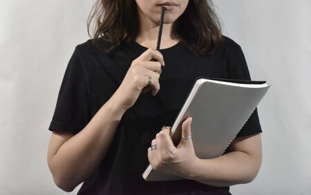 person in black shirt with notebook and pencil on the white backgtound