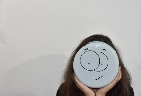 smile emoji painted on the bottom of the kitchenware and used as a mask