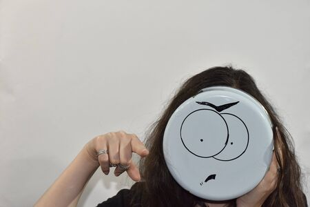 angry emoji painted on the bottom of the kitchenware and used as a mask