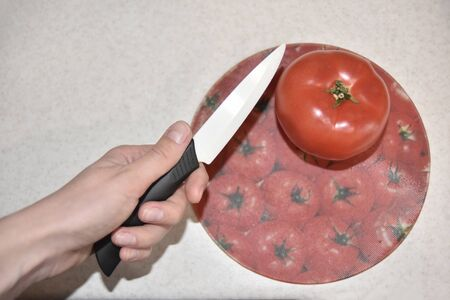 red ripe tomato on the beige table about to be cut with ceramic knife