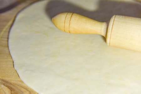 selective focus at the dough and roller at the wooden chopping board Stock fotó