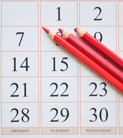 calendar and three red pencils near the last date. planning concept