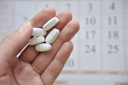 selective focus at the hand and pills with the blurred calendar at the background. scheduled treatment concept