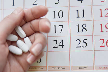 selective focus at pills and calendar with blurry hand. schedu;ed treatment concept Banque d'images