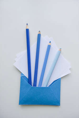 selective focus, four blue pencils and white papers out of the blue envelope Фото со стока