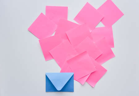 selective focus, pink paper stickers in chaos and blue envelope down on the white background