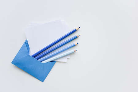 fselective focus, our blue pencils and white papers out of the blue envelope with copy space on top