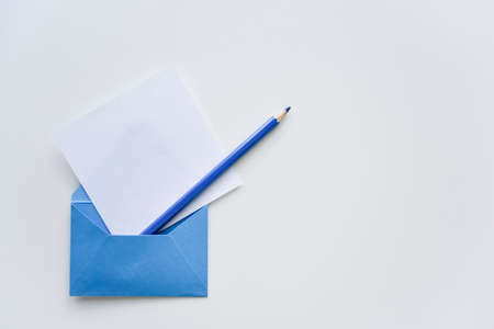 selective focus, white paper sheet and dark blue pencil out of the blue envelope