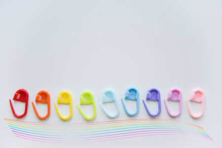 selective focus with blurry effect at colored plastic safety pins curved with the lens and rasinbow line at the bottom