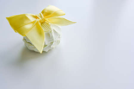 selective focus at the light green marshmallow on the light background with the yellow ribbon