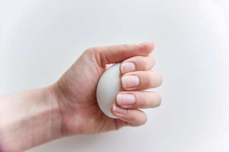 selective focus at the white chicken egg in the hand