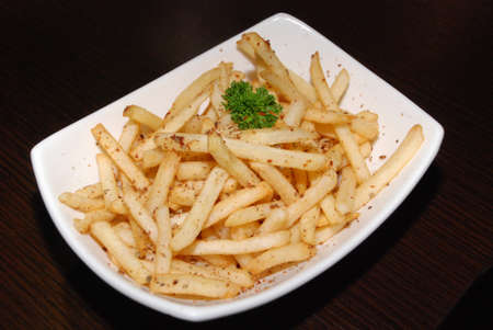 french fries with seasoning in the white rectangle bowl