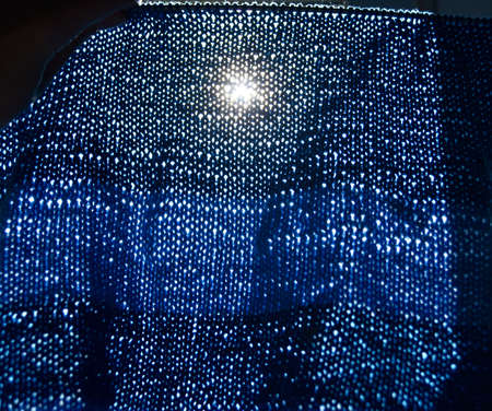 the look at the sun through the blue knitted cloth Фото со стока