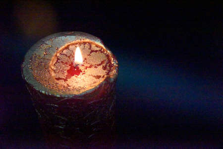 the wiew from the top at the top of the burning candle with golden layer on the red wax. Dark blue background with copy space on the side
