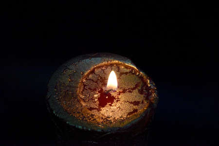 top of the burning candle with golden layer on the red wax. Dark background. Focus on the fire