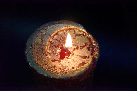 top of the burning candle with golden layer on the red wax. Dark background