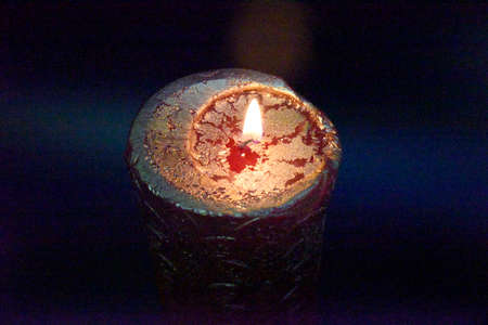 top of the burning candle with golden layer on the red wax. Dark background. Фото со стока