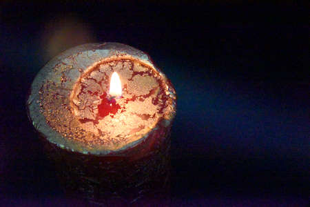 top of the burning candle with golden layer on the red wax. Dark background with copy space on the side