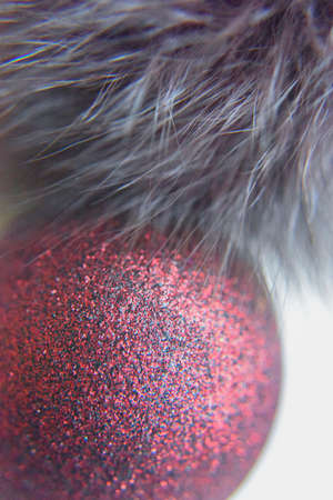 selective focus at the red ball with glitters on the surface. copy space on the white background with the gray fur Фото со стока
