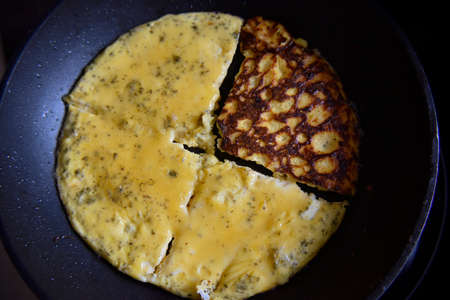 selective focus at the yellow omlet, devided on quaters on the black frying pan