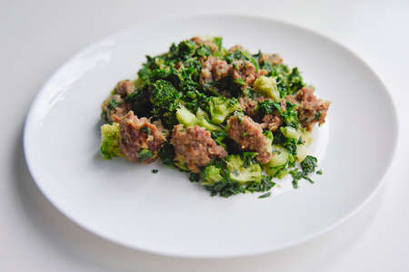 selective focus at the minced meat with spinach and broccoli on the white plate