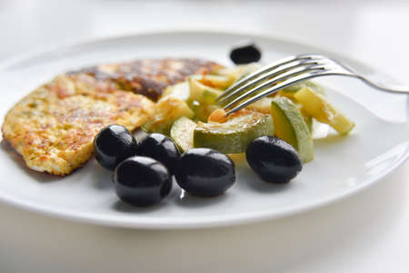 selective focus at the breakfast on the white plate. fried eggs, zucchini, black olives.
