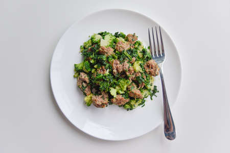 top view at the minced meat with spinach and broccoli on the white plate with fork Фото со стока