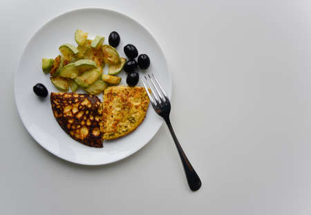 top view at the breakfast on the white plate. fried eggs, zucchini, black olives.