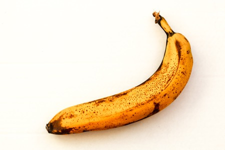 One spoiled banana lies on a white background