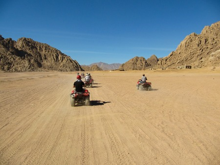 Caravan ATV racing at high speed through the desert
