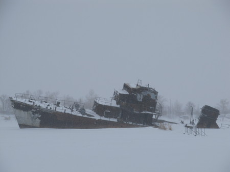 Abandoned warship at the coast of Arctic ocean in winter snowstorm.