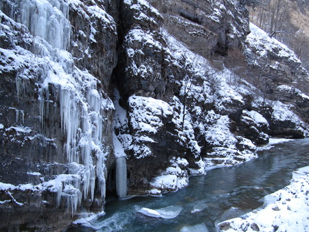 Large rock with overhanging icicles on the banks of the mountain river in winter.