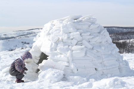 The child looks into the house of Eskimos-igloo