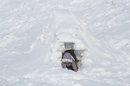 The child climbs out of the snow cave - dwelling Inuit, Igloo. Zdjęcie Seryjne