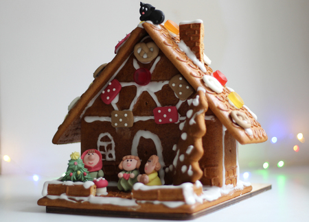 Beautiful decorated gingerbread house with various figures. On white background.