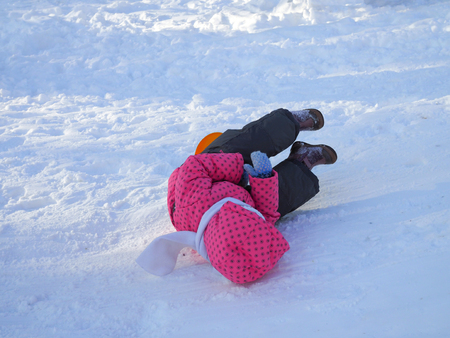The child fell down from a snowy hill on the ice in winter.