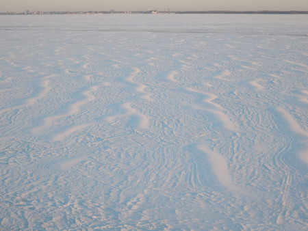 Snow surface created by a wind on the frozen river. Foto de archivo