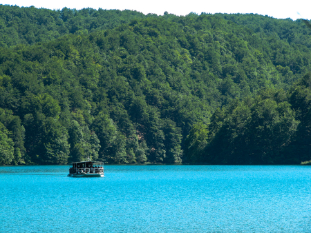 Beautiful landscape with views of the River boat floating on the turquoise clear surface of the lake in the national Park Plitvice lakes, Croatia.