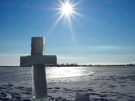 large ice cross near the hole on the background of bright blue sky and endless frozen river