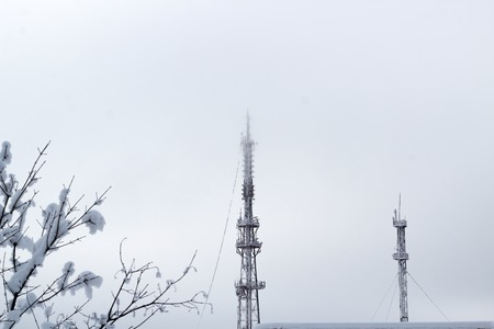 TV tower and cell tower in the fog. Misty winter morning