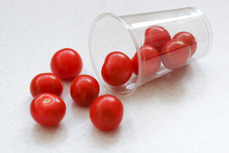 Several bright red ripe cherry tomatoes rolled out of a plastic transparent glass.
