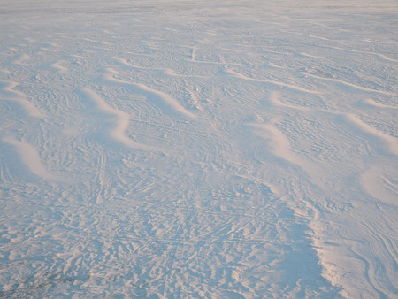 Snow surface created by a wind at sunrise.