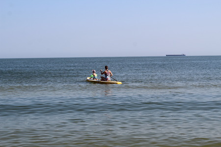 The woman and the boy floating on apaddle board on to the open sea where on the horizon a merchant ship. Water sports , active lifestyle.