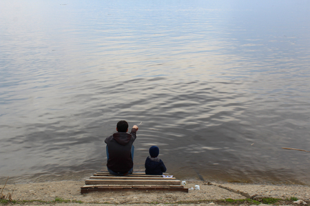 father and son sit on a wooden platform on the river Bank and look into the distance, the father shows something to the child.