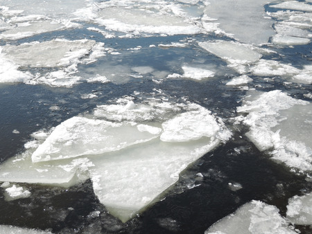 Natural ice blocks breaking up against shore and sea ice during freezing spring weather.