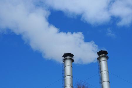 enormi tubi metallici dell'impianto rilasciano fumo bianco o vapore nell'atmosfera.