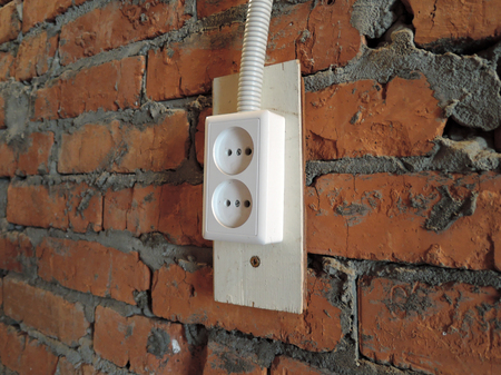 red brick wall with white electrical plug socket in garage