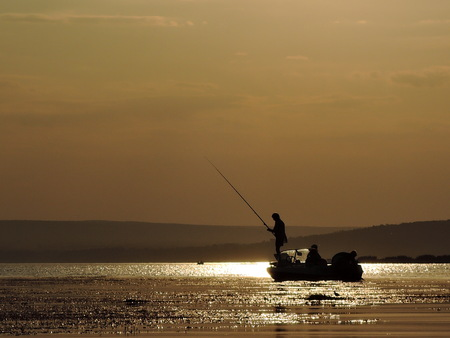 silhouette of fishermen on a boat with yellow and orange sun in the background.
